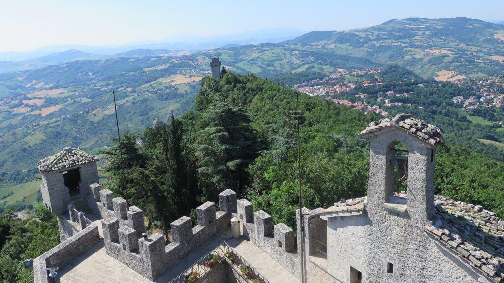 Výhľad na hradby veže Cesta, v pozadí veža Montale vykúkajúca v lese - čo vidieť v San Maríne