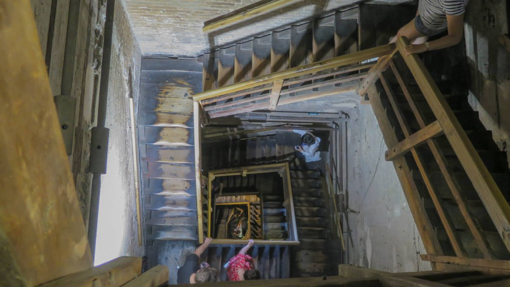Ľudia, turisti, schádzajú po obrovskom úzkom točitom drevenom schodisku vo veži Due Tori v Bologni. Pohľad zhora.