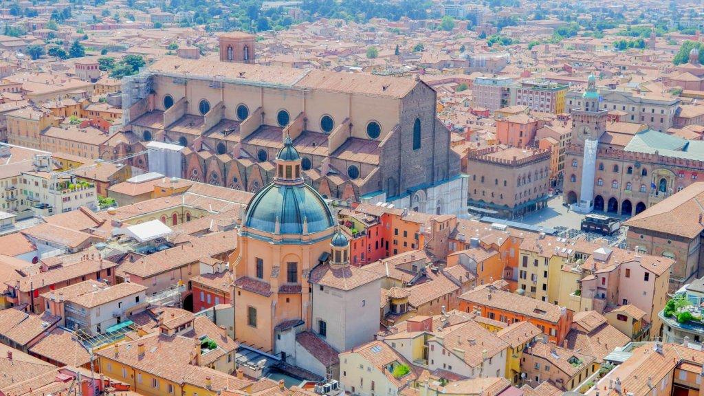 Oranžové budovy, kupola a hlavné námestie v pozadí. Výhľad z veže Due Tori v Bologni