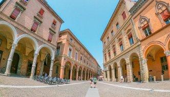 Dvojica kráča zužujúcou sa cestou medzi oranžovými budovami s ozdobnými oblúkmi