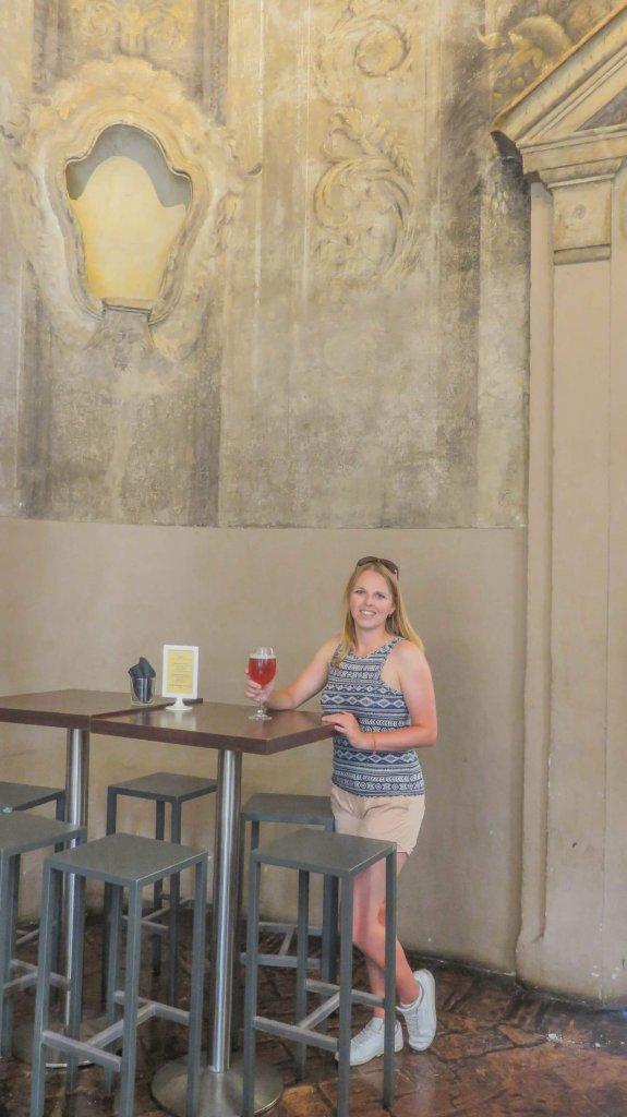 Mladá žena stojí pri barovom pulte v bare, ktorý bol kedysi kostolom. V pozadí vidno dekoračné prvky.