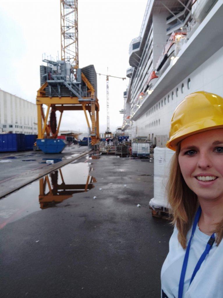 Osoba s prilbou pred loďou so žeriavom v lodeniciach