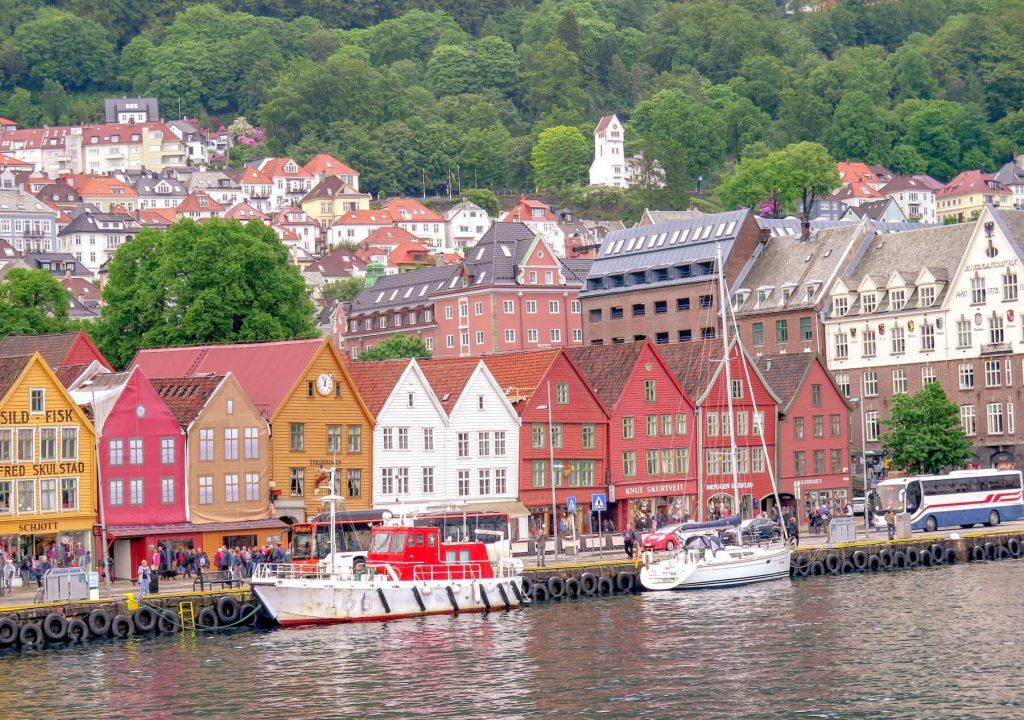 Farebné drevené domy pri vode. Pred nimi kotvia menšie lode. V pozadí je zeleň.