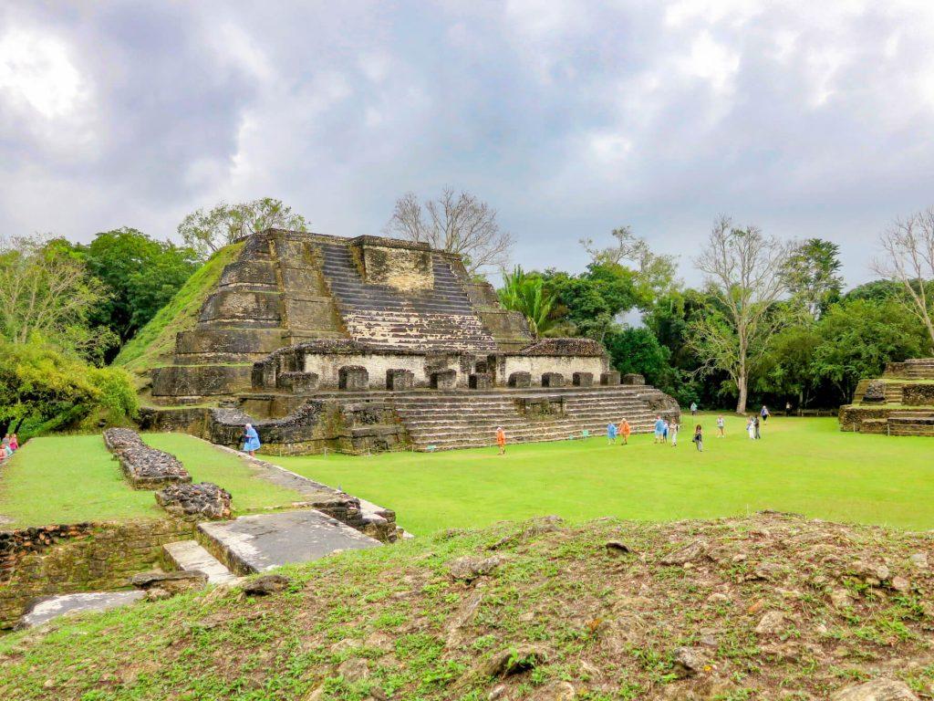 Mayská pyramída obrastená zelenou trávou, po ktorej behajú turisti v pláštenkách