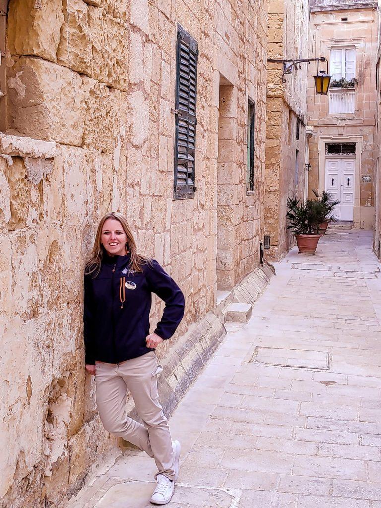 Múry starobylej ulice, o ktoré sa opriera mladá blond žena. V pozadí je vchod do domu